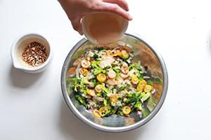 Verser la sauce sur la salade brocoli, kumquat & amandes
